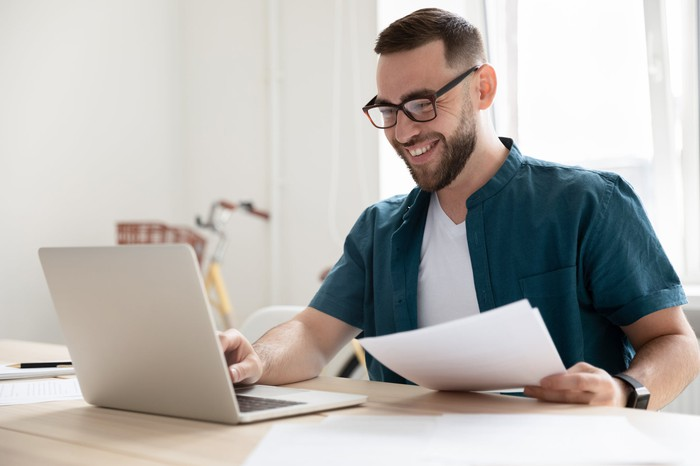 Smiling person at laptop holding documents.