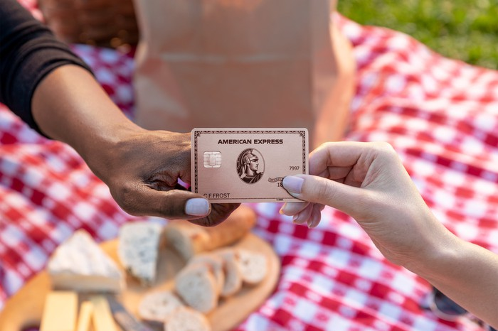 Two people exchanging an AmEx card at a picnic.