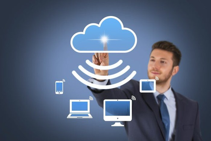 A businessman pressing a digital cloud that's sending signals to a multitude of wireless devices.