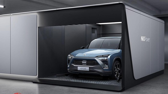 A NIO ES8 electric SUV is shown inside an automated battery-swap station.