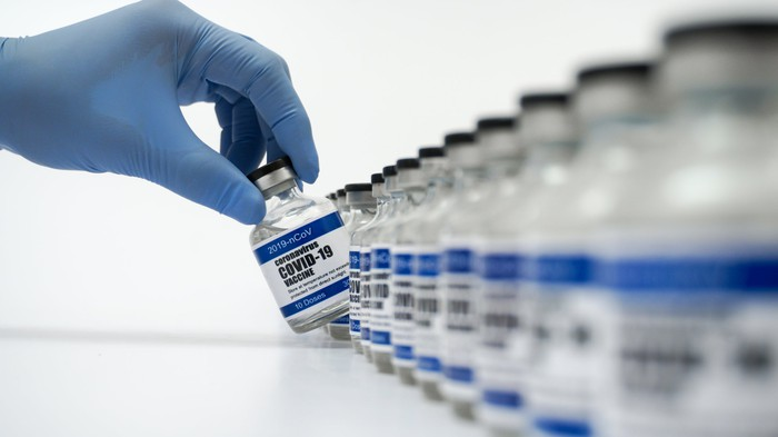 "A hand in a blue latex glove taking a bottle labeled ""COVID 19 vaccine"" out of a lineup of similar bottles."