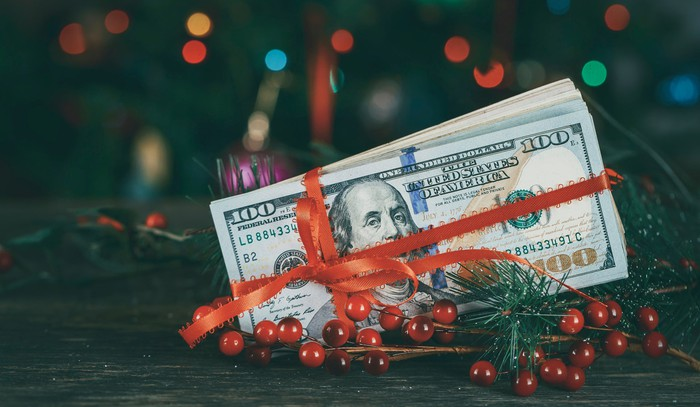 Hundred dollar bills wrapped in red ribbon sitting among Christmas decorations