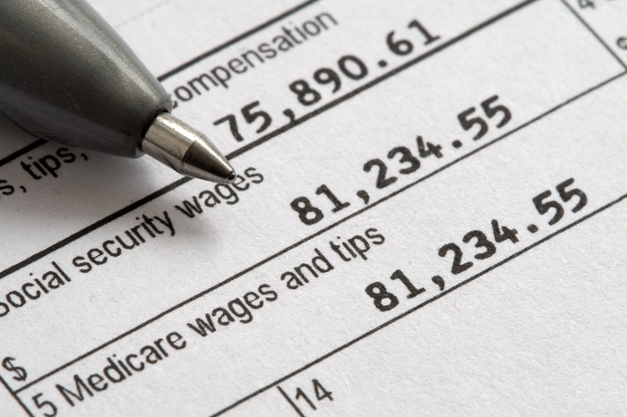 The tip of a pen pointing toward Social Security taxable wages on a W-2 tax form.
