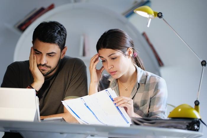 Worried couple going over paperwork