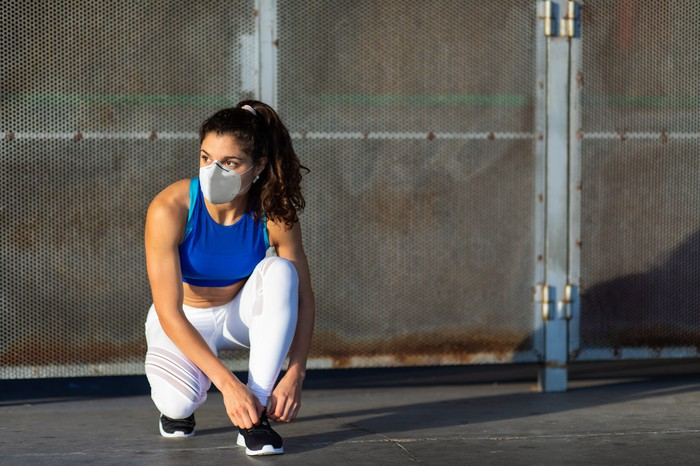 Lady wearing face mask and workout gear bending down to tie her shoelaces