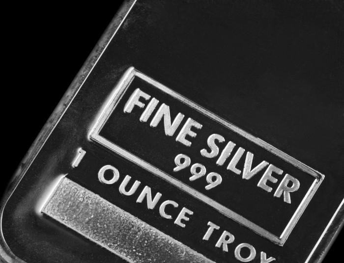A close-up of a one ounce silver ingot on a dark background.