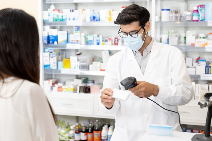 A pharmacist in a coronavirus mask scanning a prescription in front of the customer.