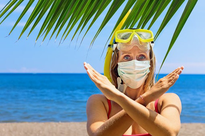 A snorkeler with her googles raised by wearing a surgical mask makes an X with her arms on the beach.