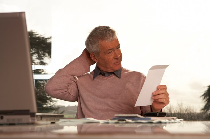 Older person at desk looking at piece of paper in hand and scratching head