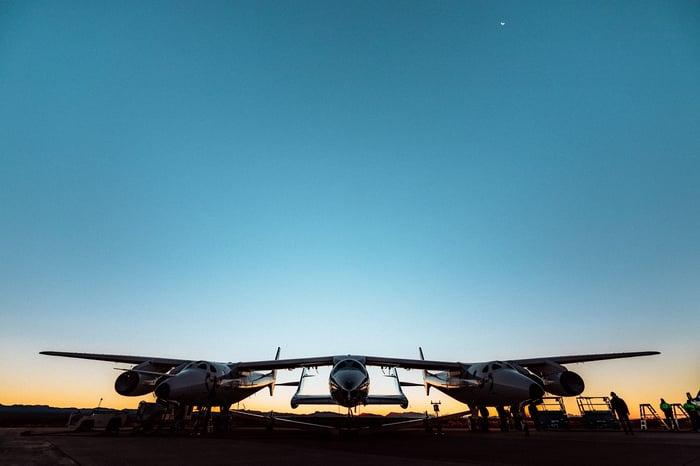Twin fuselage Virgin Galactic mothership carrying spaceplane at sunrise before test flight.