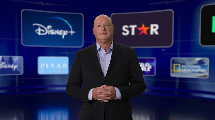 Disney CEO standing in front of a several logos of Disney assets.