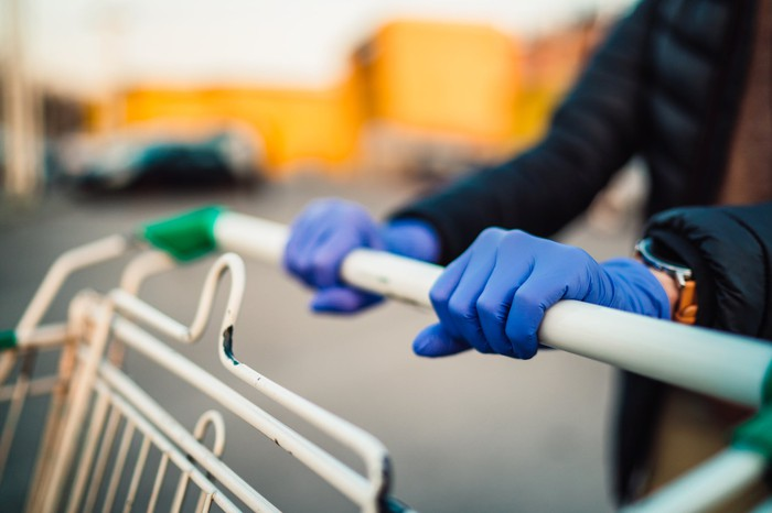 Shopping cart being pushed by gloved hands.