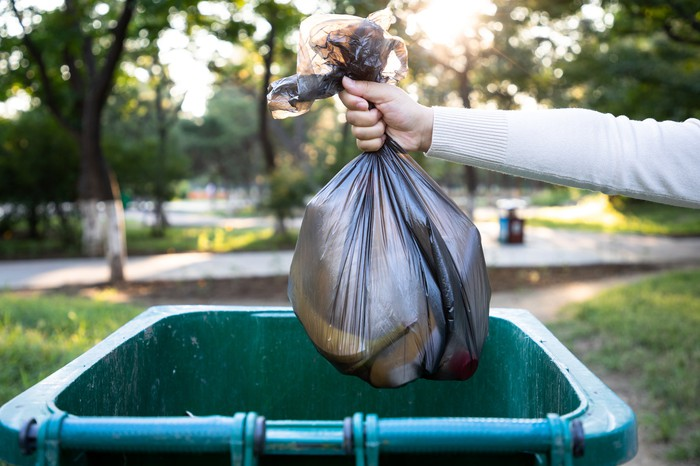 A person throws a bag of trash into a trash bin.