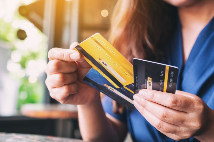 A person holding three fanned credit cards in their hands.