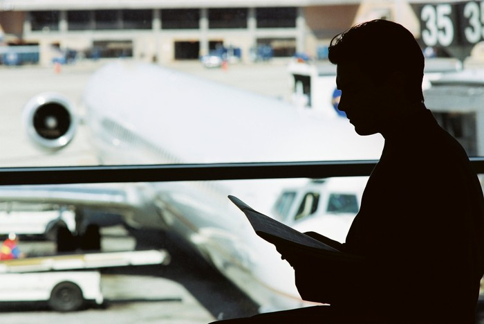 A man is silhouetted in front of an airplane parked on the tarmac.