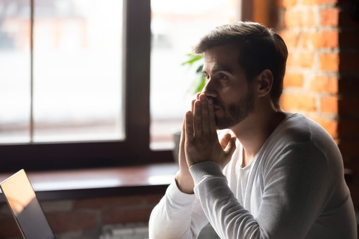 A man with his hands together in front of his face in deep thought, pondering a decision.