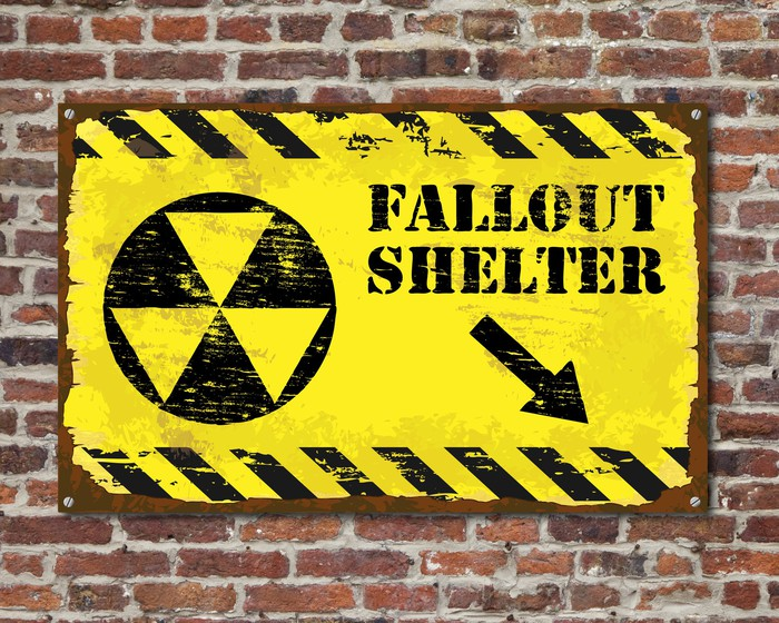 "The words ""Fallout Shelter"" printed on yellow sign against brick wall."