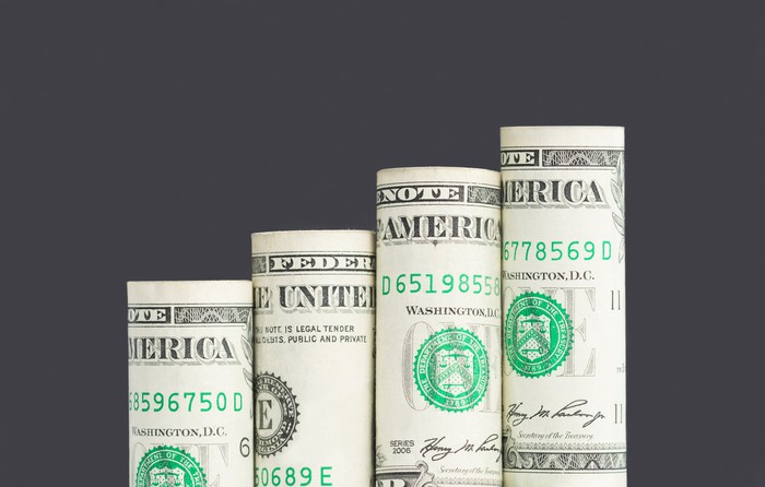 Four rolled up dollar bills stacked in a gradually ascending order of height.