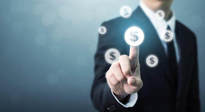 Businessman in a suit touching a floating dollar sign image with his finger.