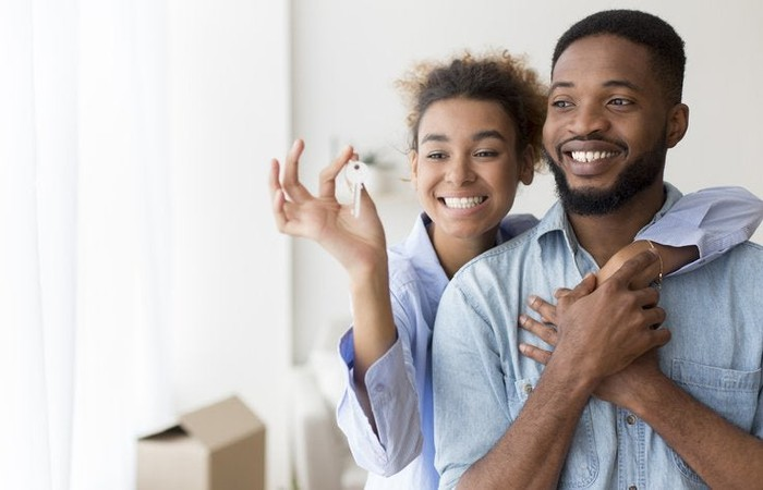 Couple smiling and holding new house keys.