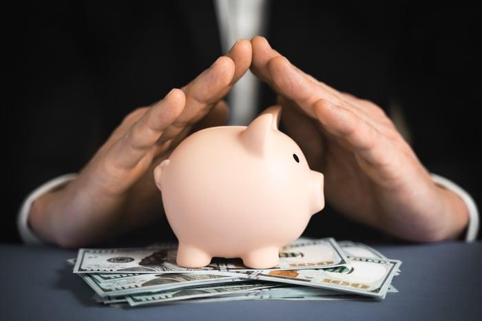 Hands over piggy bank and dollar bills