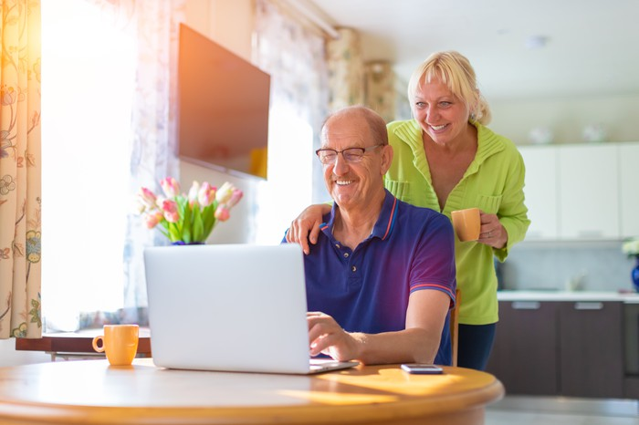 Man sitting down and woman standing behind him smile while looking at a laptop screen.