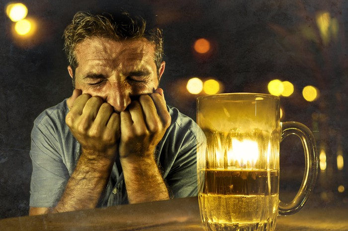 Man cringing next to a pitcher of beer