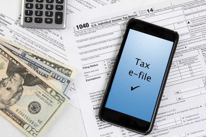 Tax forms, cash, calculator, and smartphone