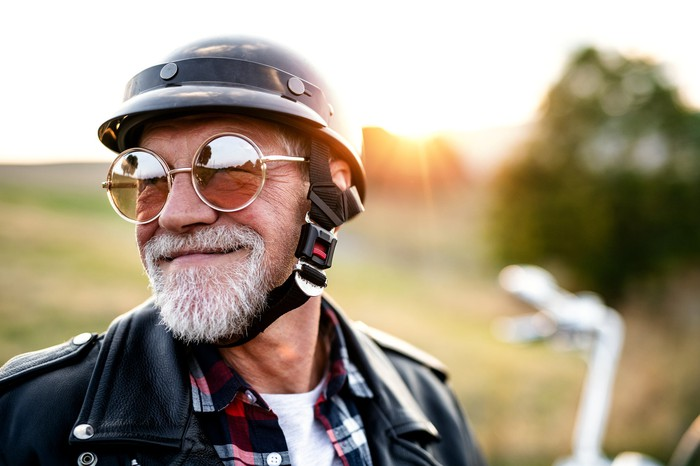 A senior citizen wearing huge round sunglasses and a helmet and leather jacket.