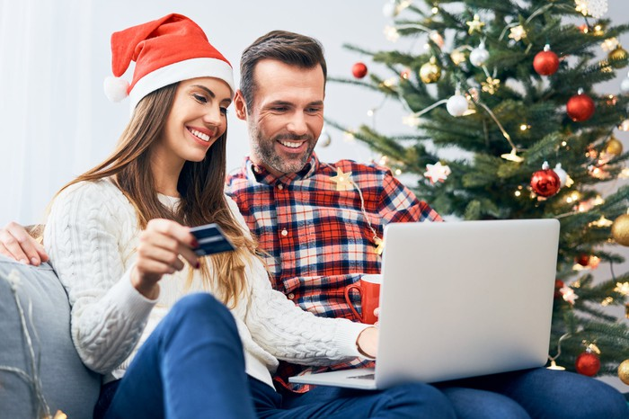 A woman in a Santa hat and a man sitting on a couch entering credit card information into a laptop with a Christmas tree in the background.