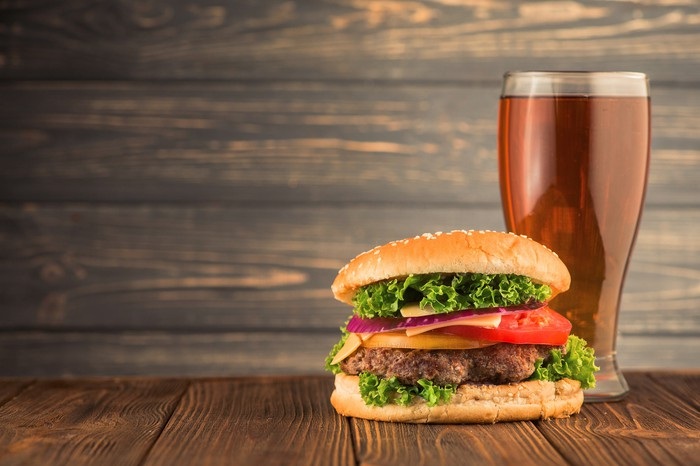 A large burger with a glass of beer.