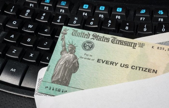 A stimulus check from the U.S. Treasury on a computer keyboard.