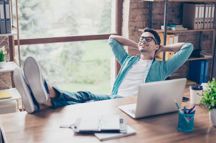 Man taking break from working on laptop with his hands resting behind his head and feet up on a desk.