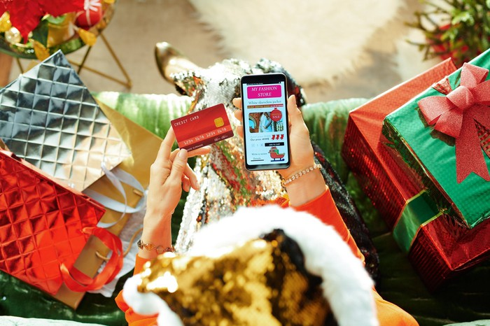 Woman using credit card to shop for Christmas gifts on smartphone while surrounded by wrapped gifts.