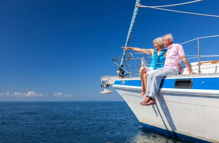 Senior couple sitting on sailboat with wife pointing at the horizon