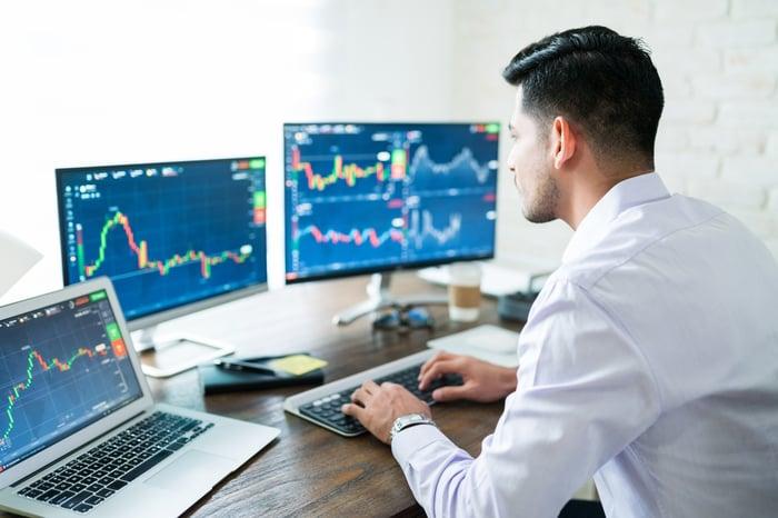 Man trading stocks with three computer monitors.
