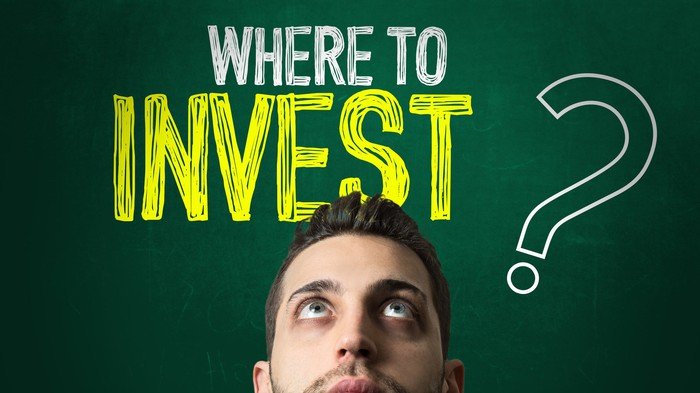 """A person looking up at the words """"Where to invest?"""" written on a chalkboard above their head."""