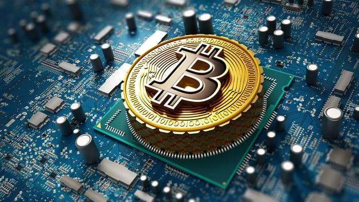 Coin with Bitcoin logo on circuit board