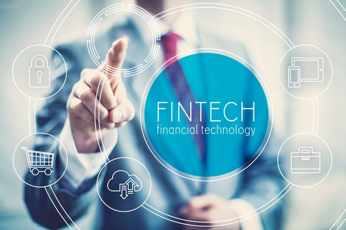A business man points at a series of digital icons representing fintech.