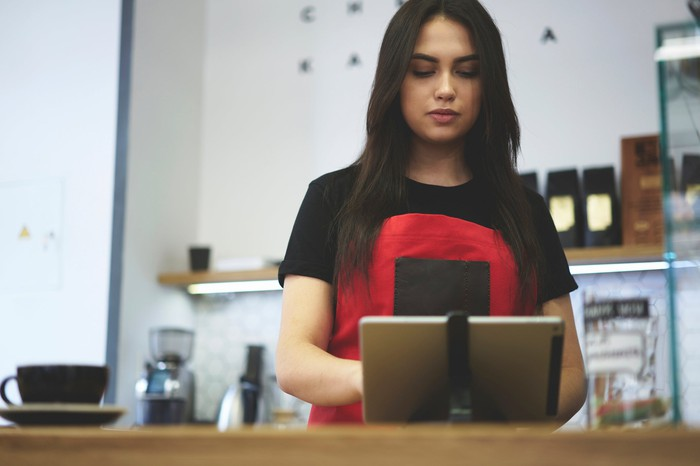 A cashier using a tablet.