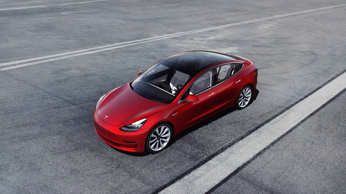 A red Tesla Model 3 driving down a deserted road.