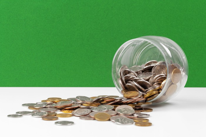 Glass jar on its side with change spilling out, against green background.