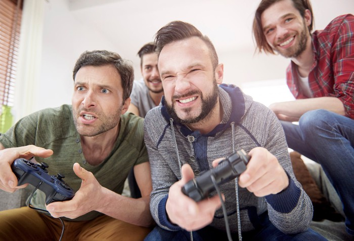 Men holding controllers play a video game together.
