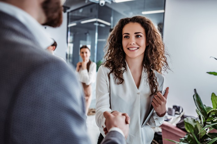 young businesswoman shaking hands with man in suit