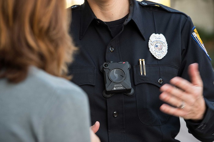 A uniformed police officer talking to a woman while wearing an Axon body camera.