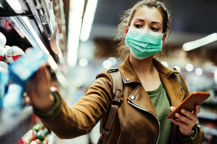 A woman in a mask shops for essentials as she checks her phone.