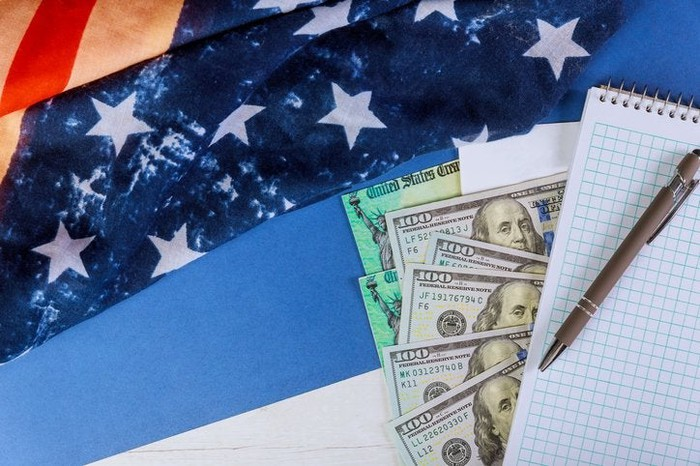 Money, checks, and a notepad atop an American flag.