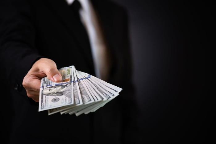 Man in suit holding out hundred dollar bills