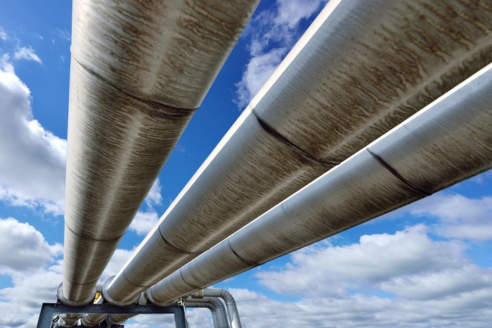 Looking upward at three oil pipelines with the sky in the background