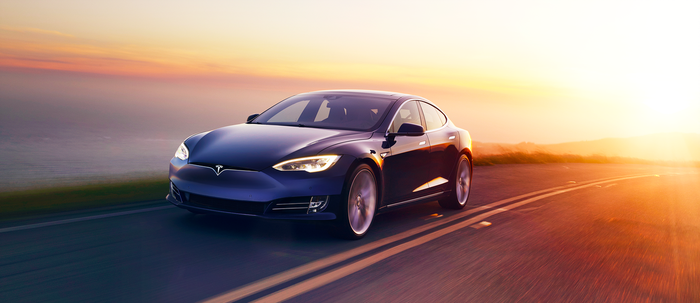 Blue Tesla Model S pointed away from a sunset on a road, with picturesque landscape nearby.